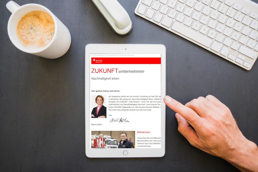 ein Schreibtisch mit einem Tablet, darauf der Firmenkunden-Newsletter der Sparkasse Hannover
